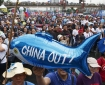 Protesters display a balloon with an anti-China message