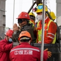 Rescue workers help a miner as he is brought to the surface on Sunday
