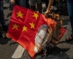 Filipinos burn a mock Chinese flag with a collage of the faces of Philippine President Rodrigo Duterte and Chinese President Xi Jinping