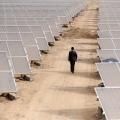 A man walks among solar panels at a solar power plant under construction in Aksu, Xinjiang in the Uighur Autonomous Region