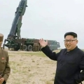 North Korea's Kim Jong Un in front of a missile launcher