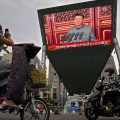 A woman on her electric-powered scooter films a large video screen outside a shopping mall showing Chinese President Xi Jinping speaking