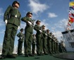 Members of the Chinese Coast Guard stand in formation on board their vessel after it anchored at Manila port